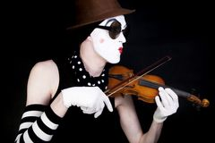Mime playing on small violin in sunglasses Stock Photos