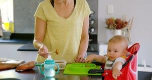 Mime a preparar el desayuno para su bebé en la cocina 4k almacen de video