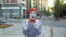 Mime in red beret and stripped shirt show two signs okey on camera. Funy mime in red beret and stripped shirt is posing for camera at fountains background stock footage