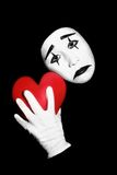 Mime with red heart. Actor mime with black and white make-up holding red heart in the hand. Isolated on black background Stock Image