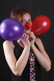 Mime with red nose and baloons. Young girl as mime with red nose and twoo baloons Royalty Free Stock Images
