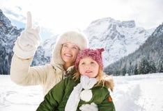 Mime a señalar para arriba en algo al niño en invierno al aire libre Fotos de archivo libres de regalías