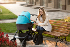 Mime a sentarse en banco y a mirar a su bebé en cochecito Imágenes de archivo libres de regalías