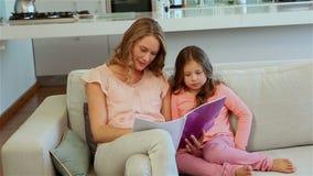 Mime a sentarse en el sofá con su hija almacen de metraje de vídeo
