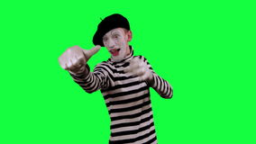 The mime shows thumb down. The boy mime against a green background stock video