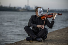Mime sitting on riverside and playing violin outdoors Stock Photo