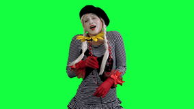 The mime sniffs and gives a flower. The girl mime against a green background stock footage