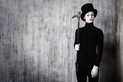 Mime and a stick. Elegant expressive male mime artist posing with walking stick by a grunge wall Stock Image