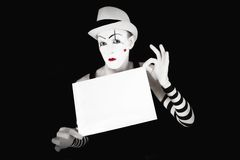 Mime in striped gloves holding white  blank Stock Image