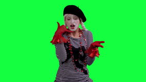 The mime talks on cell phone invisible. The girl mime against a green background stock footage