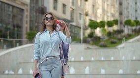 Mime tem o divertimento perto da mulher à moda que usa o telefone vídeos de arquivo