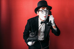 Mime theater actor performing with old telephone. Comedy pantomime artist in suit, gloves and hat royalty free stock photography