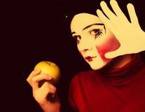 Mime triste con una manzana en un fondo negro Fotos de archivo libres de regalías