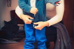 Mime a vestir para arriba a su hijo en ropa del invierno Foto de archivo