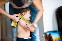 Mime a vestir a su pequeño hijo que esté llorando Imagen de archivo