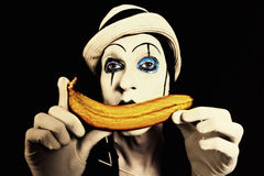 Mime in white hat holding a banana in his hand Stock Photos