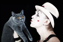 Mime in white hat holding gray cat British Royalty Free Stock Photography