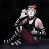 Mime in white hat with red flower sits on the floor Royalty Free Stock Photos
