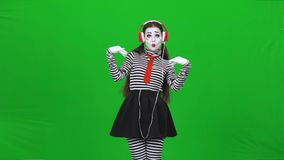 Mime woman listening to the music through headphones. Chroma key. Mime woman with professional make-up, dressed in striped turtleneck and leggings is acting stock footage