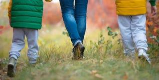 Mime y dos hijos que caminan en el parque del otoño que lleva a cabo las manos Los pies se cierran para arriba imágenes de archivo libres de regalías
