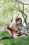 Mime y dos niños en jardín floreciente con los huevos de Pascua Imagen de archivo