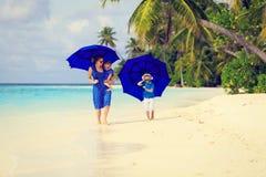 Mime y dos niños en la playa con los paraguas Imagenes de archivo