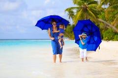 Mime y dos niños en la playa con los paraguas Fotos de archivo libres de regalías