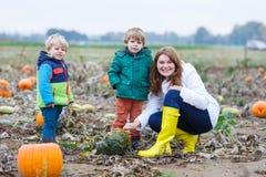 Mime y dos pequeños hijos que se divierten en remiendo de la calabaza. Fotografía de archivo