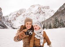 Mime y sorprendió al niño que comprueba las fotos en invierno al aire libre fotos de archivo libres de regalías