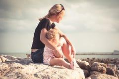 Mime y su bebé que se sienta junto en la costa de la playa durante puesta del sol y que mira en la distancia Imagenes de archivo