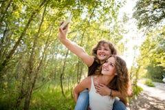 Mime y su hija del adolescente que toma el selfie con el teléfono móvil Fotos de archivo libres de regalías