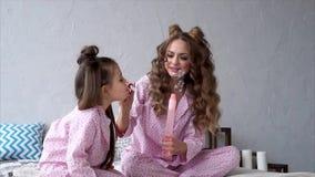 Mime y su hija que esté llevando burbujas de jabón del soplo de los pijamas en el dormitorio metrajes
