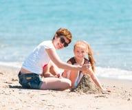 Mime y su hija que juega en la arena Fotos de archivo