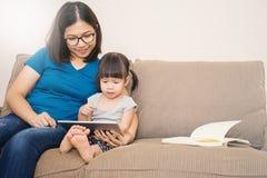Mime y su hija que mira la tableta Fotos de archivo libres de regalías