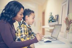 Mime y su hijo que mira algo en el ordenador portátil Africano América Imagen de archivo libre de regalías
