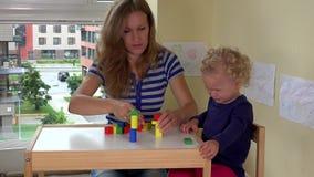Mime y su niña pequeña que juega con los juguetes de madera de los ladrillos en la pequeña tabla metrajes