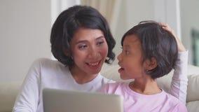 Mime y su ordenador portátil del uso de la hija en el sofá metrajes