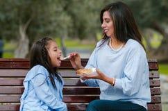 Mime y su pequeña hija que se sienta en un banco en el parque fotografía de archivo