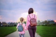 Mime y su poco dauther con la mochila que camina en día de verano Visión desde una parte posterior imagen de archivo