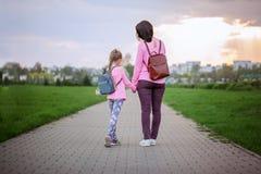 Mime y su poco dauther con la mochila que camina en día de verano Visión desde una parte posterior imagen de archivo libre de regalías