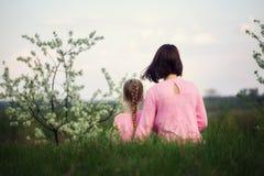 Mime y su poco dauther que se sienta en hierba en día de verano Visión desde una parte posterior fotos de archivo libres de regalías