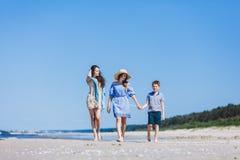 Mime y sus dos niños que caminan en la playa imágenes de archivo libres de regalías