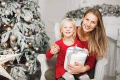 Mime y sus hijas que abren el presente de cumpleaños del ` s de la niña fotografía de archivo libre de regalías