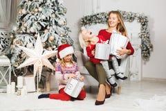 Mime y sus hijas que abren el presente de cumpleaños del ` s de la niña foto de archivo