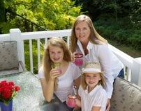 Mime y sus hijas que beben el jugo de pomelo mientras que es al aire libre Foto de archivo