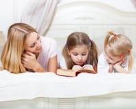 Mime y sus hijas que leen el libro de la historia del tiempo de la cama Imágenes de archivo libres de regalías