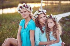 Mime y sus hijas que se relajan al aire libre mientras que se sienta en una trayectoria de madera en un campo en la puesta del so Fotografía de archivo