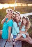 Mime y sus hijas que se relajan al aire libre mientras que se sienta en una trayectoria de madera en un campo en la puesta del so Imágenes de archivo libres de regalías