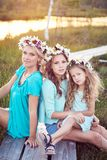 Mime y sus hijas que se relajan al aire libre mientras que se sienta en una trayectoria de madera en un campo en la puesta del so Imagen de archivo