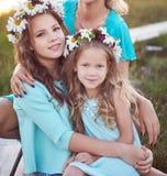 Mime y sus hijas que se relajan al aire libre mientras que se sienta en una trayectoria de madera en un campo en la puesta del so Fotografía de archivo libre de regalías